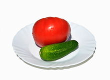Fresh tomato with cucumber. On white dish Stock Images