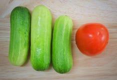 Fresh Tomato with Cucumbers on Cutting Board. Vegetable, Fresh Ripe Tomato with Cucumbers on A Wooden Cutting Board Royalty Free Stock Photo