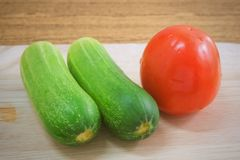 Fresh Tomato with Cucumbers on Cutting Board. Vegetable, Fresh Ripe Tomato with Cucumbers on A Wooden Cutting Board Royalty Free Stock Photos