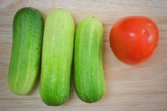 Fresh Tomato with Cucumbers on Cutting Board. Vegetable, Top View of Fresh Ripe Tomato with Cucumbers on A Wooden Cutting Board Stock Photography