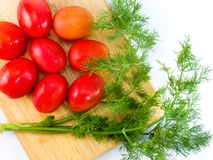Fresh tomato and dill wooden chopping board on white background. Royalty Free Stock Photo