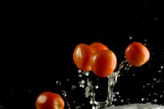 Fresh tomato dropped into water, stock photo