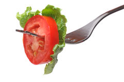 Fresh Tomato On Fork. Slice of a fresh tomato and salad on fork, isolated on white background Royalty Free Stock Photos