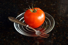 Fresh tomato on the glass plate. Stock Photography