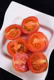 Fresh Tomato Halves. Fresh, juicy red tomatoes, cut in half on a white plate Royalty Free Stock Photo
