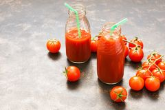 Fresh tomato juice in glass bottles and cherry tomatoes on a dark background. Selective focus, copy space. Royalty Free Stock Photography