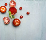 Fresh tomato juice in a glass with a straw, with green leaf, chopped tomatoes spread around border ,text area wooden rusti Stock Photography