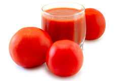 Fresh tomato juice in glass and tomatoes. Fresh tomato juice and tomatoes on isolated background Royalty Free Stock Photo