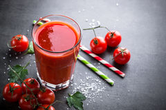 Fresh tomato juice. And ingredients at dark slate table. Copy space Stock Image
