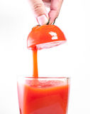 Fresh tomato juice pouring into glass Stock Image