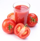 Fresh tomato juice and ripe tomatoes round glass. stock image