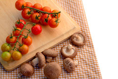 Fresh tomato and mushroom on wooden plate Royalty Free Stock Photo