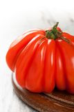 Fresh tomato on old wooden board. Stock Image