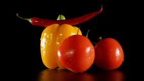 Fresh tomato and pepper rotate on a black background with water drops Stock Photos