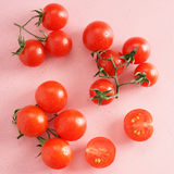 Fresh tomato. On pink background with drops of dew Stock Photos
