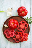 Fresh tomato on a plate. Fresh red tomato on a plate with garlic Royalty Free Stock Photo