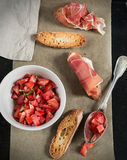 Fresh tomato salad with basil, toasts and ham. Fresh tomato salad with basil and spices and bread toasts and ham. Vignetting stock image