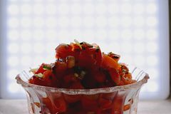 Fresh tomato salsa against a bright white light. A fresh diced tomato salsa with chives and oil in a decorative glass serving dish/bowl. Image set against a royalty free stock photos