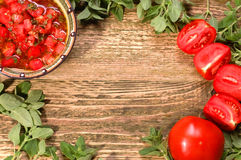 Fresh tomato salsa with herbs on a wooden table Stock Images
