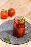 Fresh tomato smoothie with basil leaves and straw on tabletop Stock Image