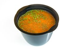 Fresh tomato soup was seasoned with finely chopped, dried parsley. In a black take-out package Stock Photography