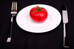 Fresh tomato on a white plate Royalty Free Stock Photography