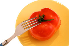 Fresh tomatoe and fork. Image of a fresh tomatoe placed on yellow plate and a fork on the top Royalty Free Stock Images