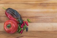 Tomato and Peppers on a Cutting Board. A fresh tomatoe, poblano, and some small chilis seen from above on a wooden cutting board Stock Photo