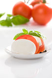 Fresh tomatoes. Slices with cottage cheese on white plate. Some tomatoes and basil in background. All on white stock images