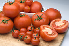 Fresh tomatoes. Plenty of fresh ripe tomatoes on the wooden board. One is cut in half Stock Image