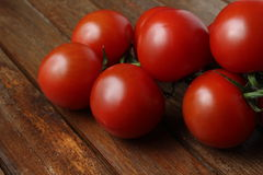 Fresh tomatoes 4. Some fresh bright tomatoes in front of a wooden background royalty free stock photography