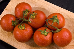 Fresh tomatoes. On wooden chopping board Royalty Free Stock Photos