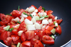 Fresh tomatoes. Some fresh tomatoes with onions in a pan Royalty Free Stock Photography