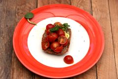 Fresh tomatoes and avocado on wholemeal toast, topped with fresh basil. Tomatoes drenched in olive oil, with ripe avocados and basil leaf, served on wholemeal royalty free stock photos