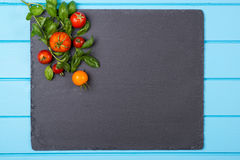Fresh tomatoes and basil on the black slate. . Space for text. Royalty Free Stock Images