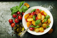 Fresh tomatoes with basil leaves in a bowl Stock Photography