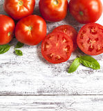 Fresh tomatoes and basil on wooden background Stock Photo