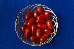 Fresh tomatoes in a basket on a blue background Royalty Free Stock Photo