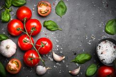 Fresh tomatoes on black slate background. Fresh cherry tomatoes with basil garlic and sea salt on black slate background. Cooking ingredients Top view Royalty Free Stock Photography