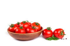Fresh tomatoes in a bowl with basil isolated Stock Image