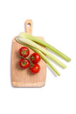 Fresh tomatoes and celery sticks on chopping board Royalty Free Stock Photo