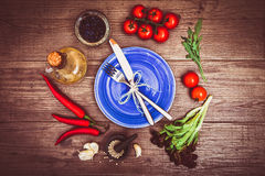 Fresh tomatoes, chili pepper and other spices and herbs around modern blue plate in the center of wooden table. Top view. Royalty Free Stock Images