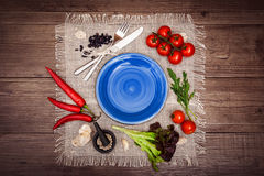Fresh tomatoes, chili pepper and other spices and herbs around modern dark blue plate in the center of wooden table and cloth napk. In. Top view. Blank place for Stock Photos