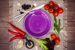 Fresh tomatoes, chili pepper and other spices and herbs around modern purple plate in the center of wooden table and cloth napkin. Stock Photo