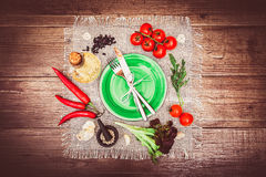 Fresh tomatoes, chili pepper and other spices and herbs around modern Turquoise plate in the center of wooden table and cloth napk Stock Photos