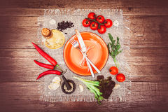 Fresh tomatoes, chili pepper and other spices and herbs around modern Turquoise plate in the center of wooden table and cloth napk Stock Photography