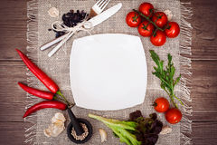 Fresh tomatoes, chili pepper and other spices and herbs around modern white square plate in the center of wooden table and cloth n Stock Image