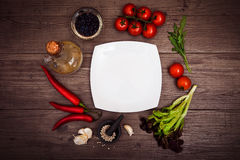 Fresh tomatoes, chili pepper and other spices and herbs around modern white square plate in the center of wooden table and cloth n Stock Photography