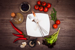 Fresh tomatoes, chili pepper and other spices and herbs around modern white square plate in the center of wooden table. Top view. Fork and knife on plate royalty free stock image