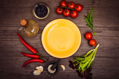 Fresh tomatoes, chili pepper and other spices and herbs around modern yellow plate in the center of wooden table. Top view. Copy s. Fresh tomatoes, chili pepper Stock Photography